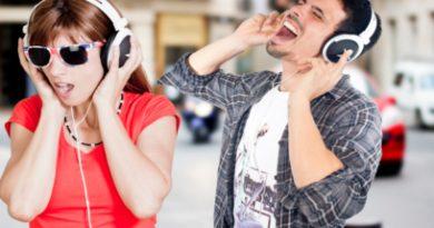 Happy people with headphones on street