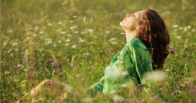 Young beautiful woman enjoying nature in the flowers field